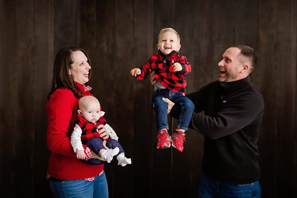 family-with-two-small-children-with-dark-wood-backdrop-in-south-jersey-photography-studio