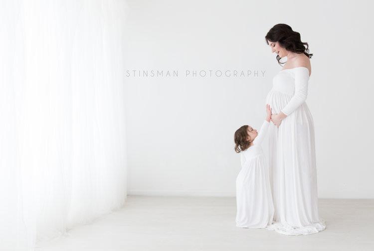 little sister holding mom pregant belly