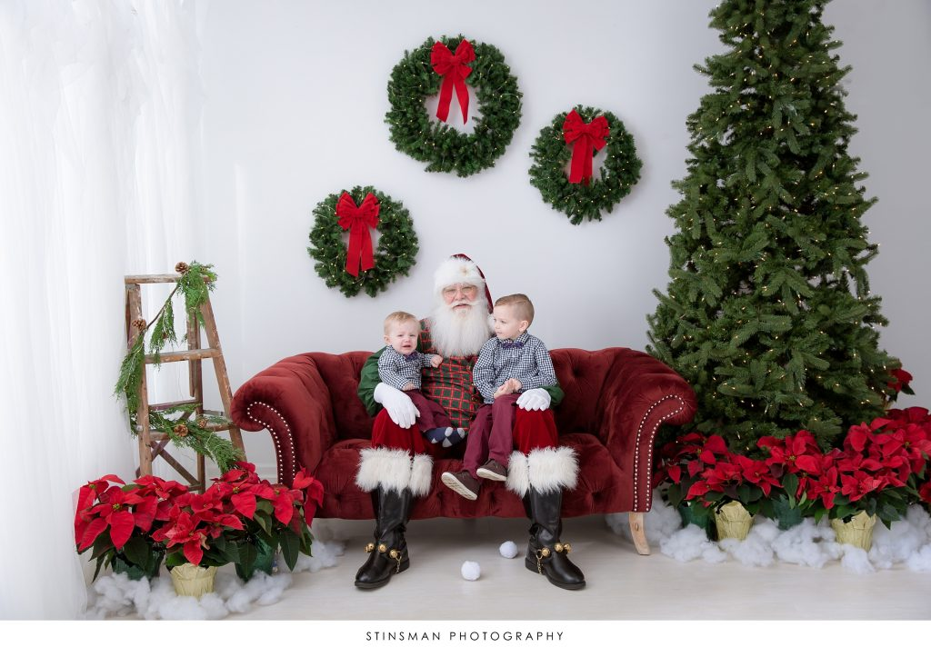 santa sitting with children looking at the camera
