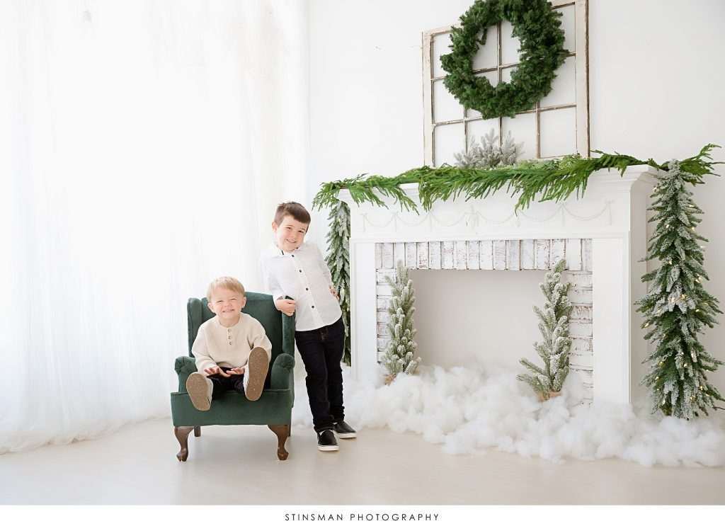 two brothers sitting in a christmas mini session set