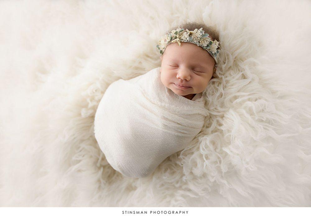 Newborn baby girl swaddled in white during newborn photoshoot