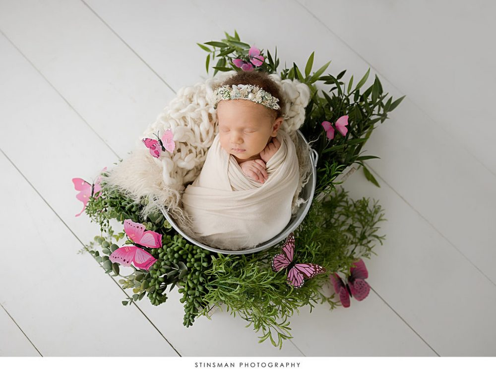 Newborn baby girl sleeping in bucket surrounded by butterflies in newborn photoshoot