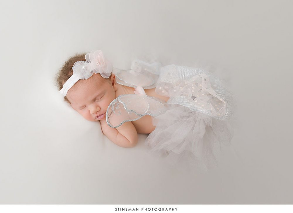 Newborn baby girl sleeping in butterfly outfit during photoshoot