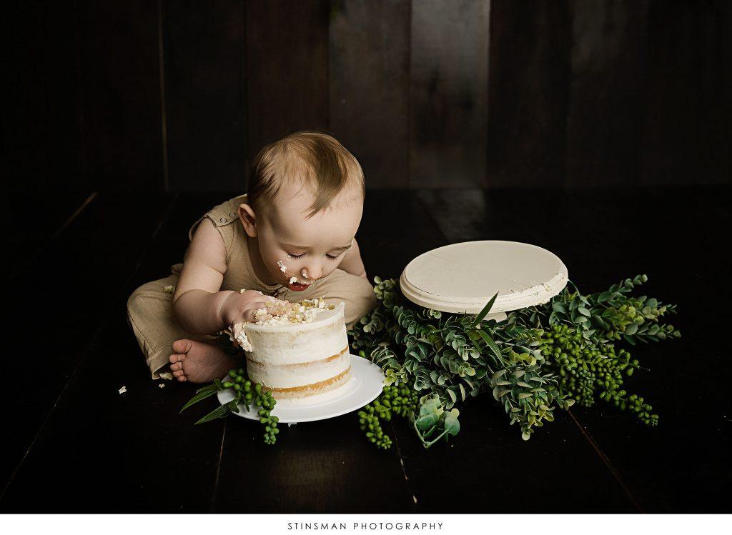1 year old baby boy eating his cake in cake smash photo shoot