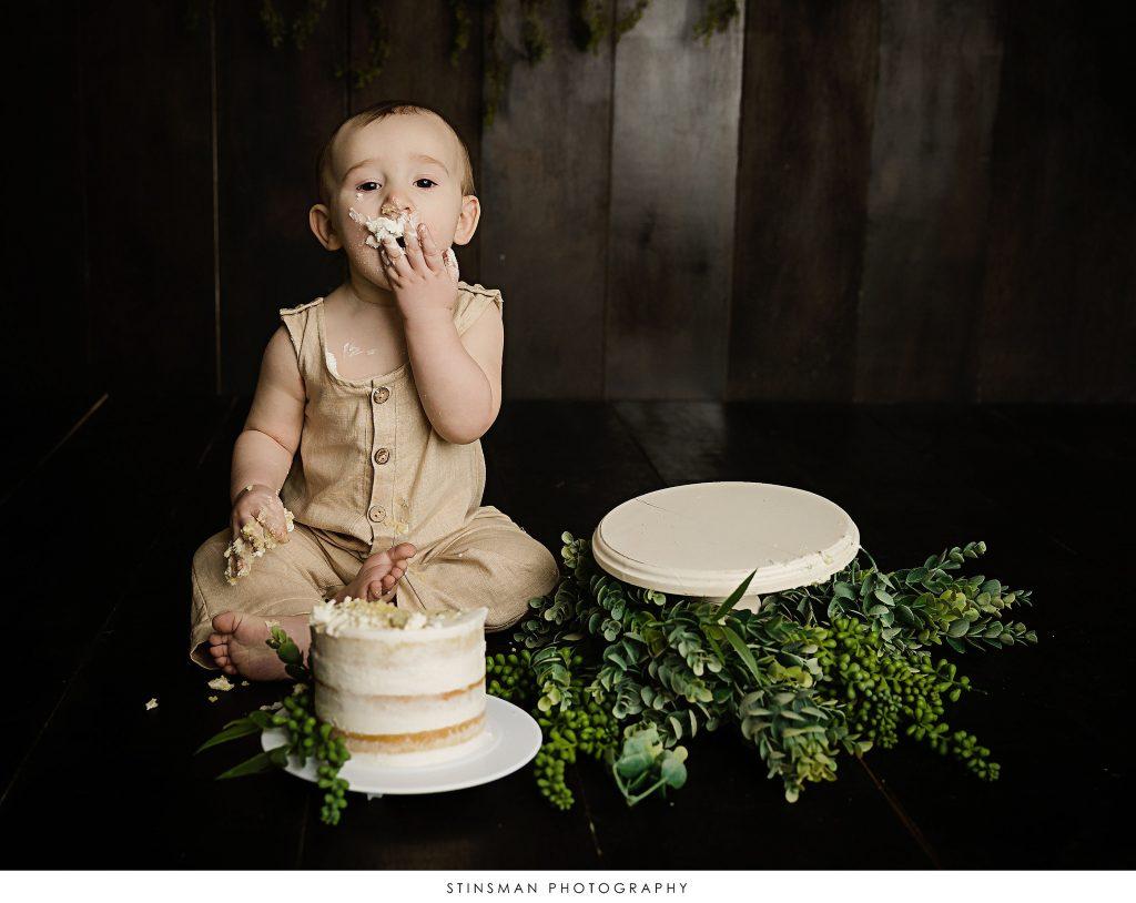1 year old baby boy eating his cake during cake smash photoshoot.