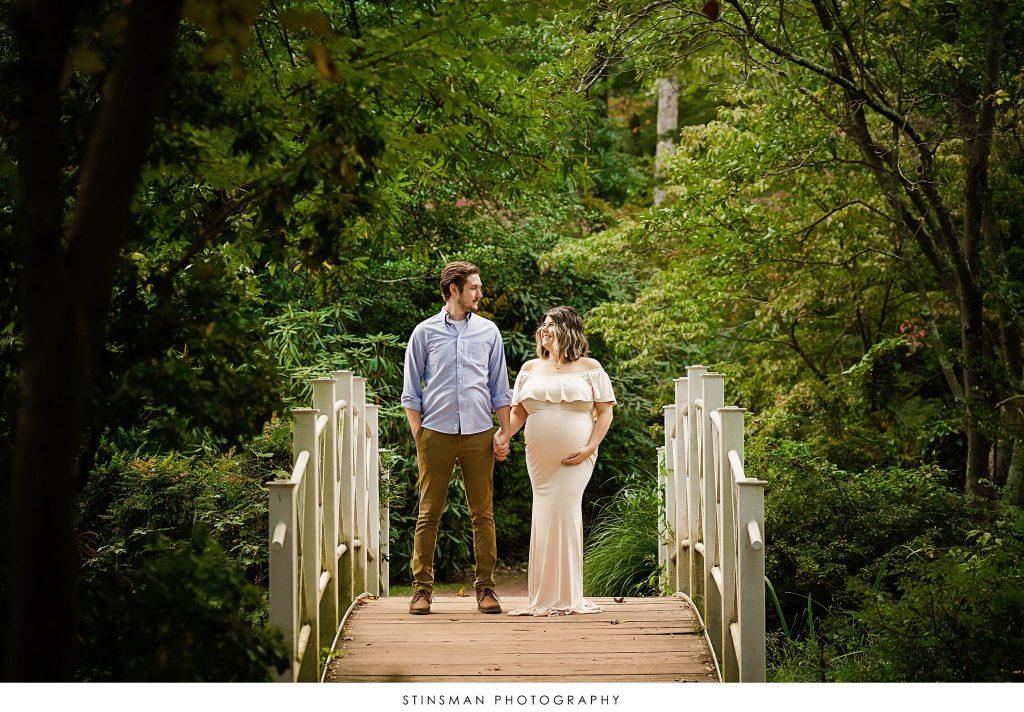 Pregnant mom and dad posing on a bridge at their maternity photoshoot
