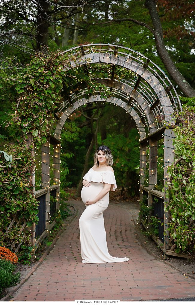 Pregnant mom posed under a lit walkway at her maternity photoshoot