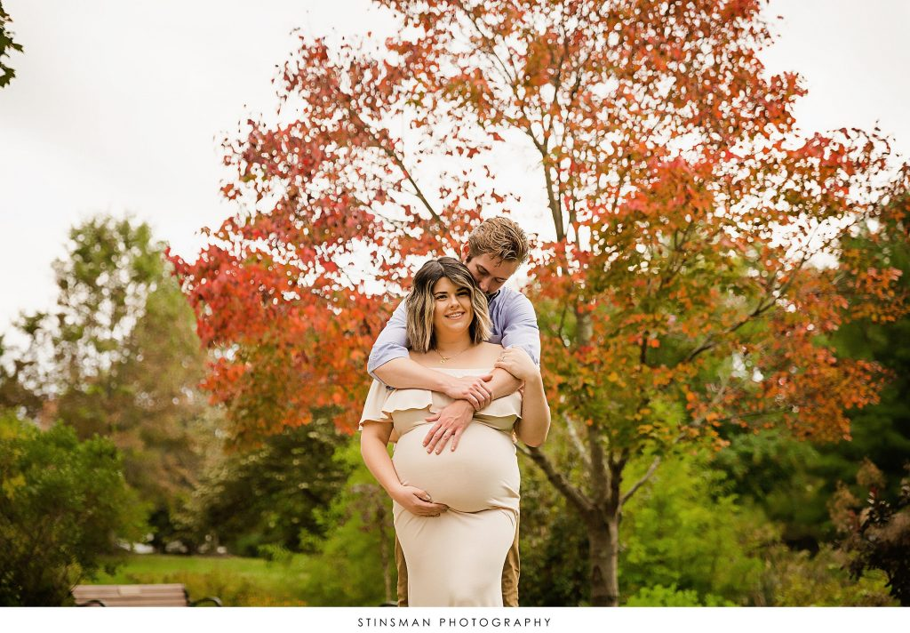Pregnant mom and dad posed with fall colors at their maternity photoshoot