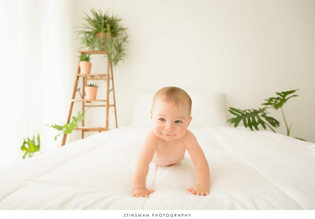 Baby boy crawling on a white bed at his sitter session