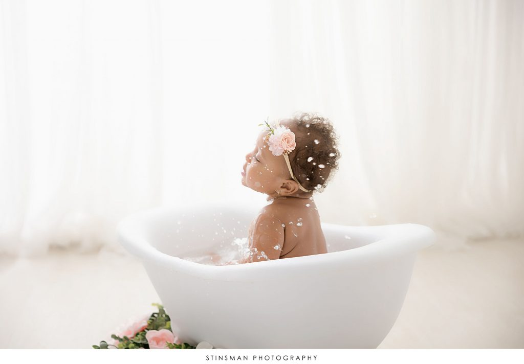 Baby girl playing in the tub at her one year old milestone photoshoot