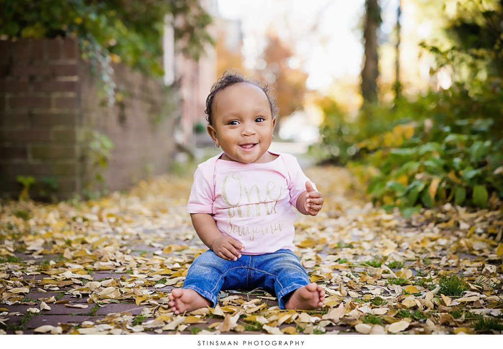 Baby girl in fall foliage at her one year milestone photoshoot