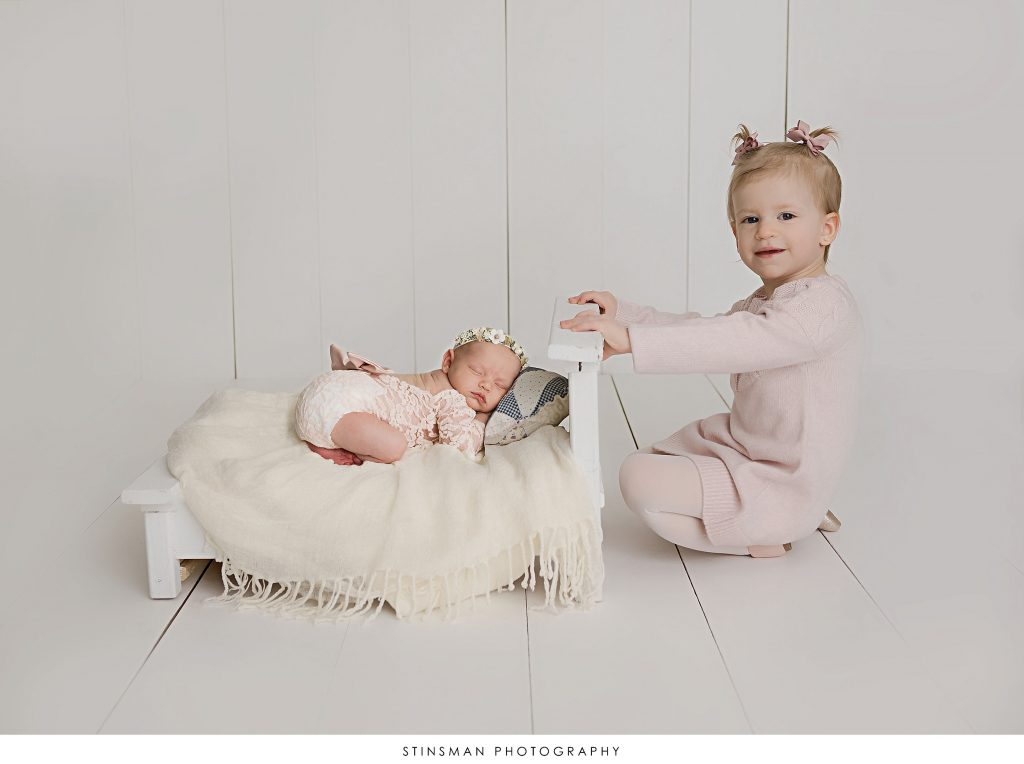 Siblings in a composite photo at their newborn photoshoot