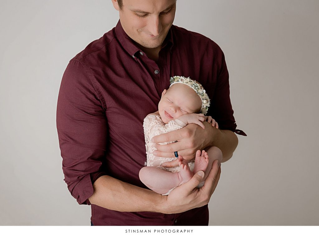 Dad with his newborn baby girl smiling at their newborn photoshoot