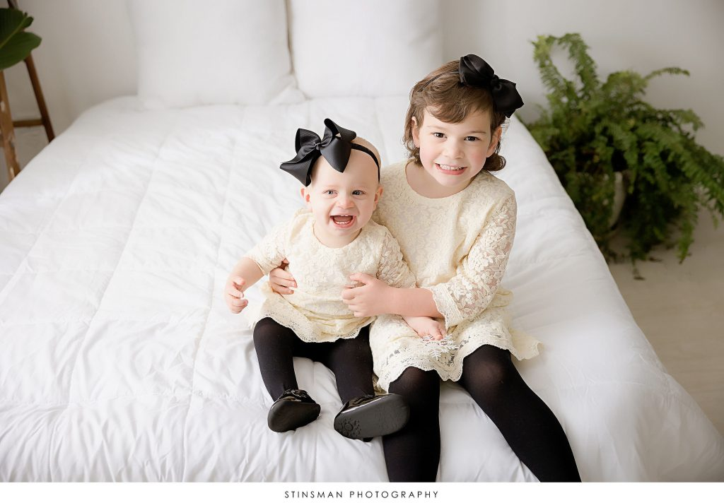 Sisters sitting on a bed during their family photoshoot