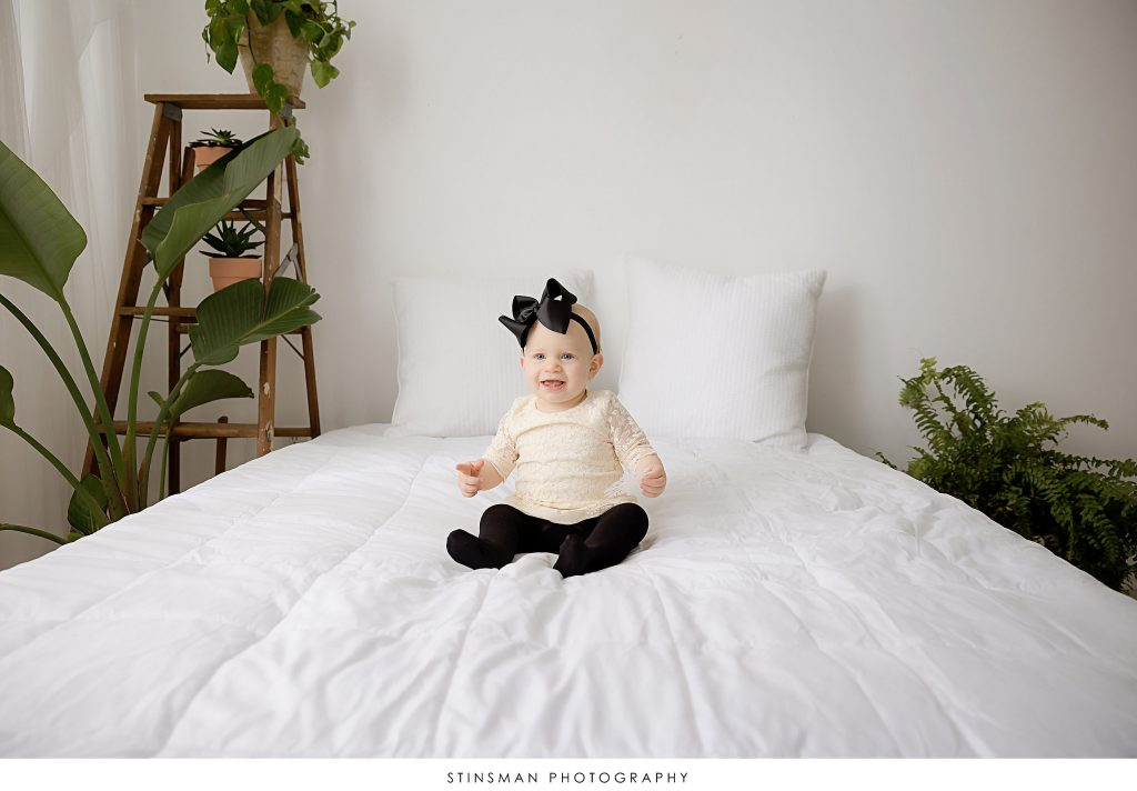Baby smiling on a bed during her 1 year milestone photoshoot