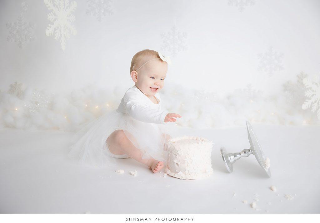 Baby girl smiling at her cake smash photoshoot