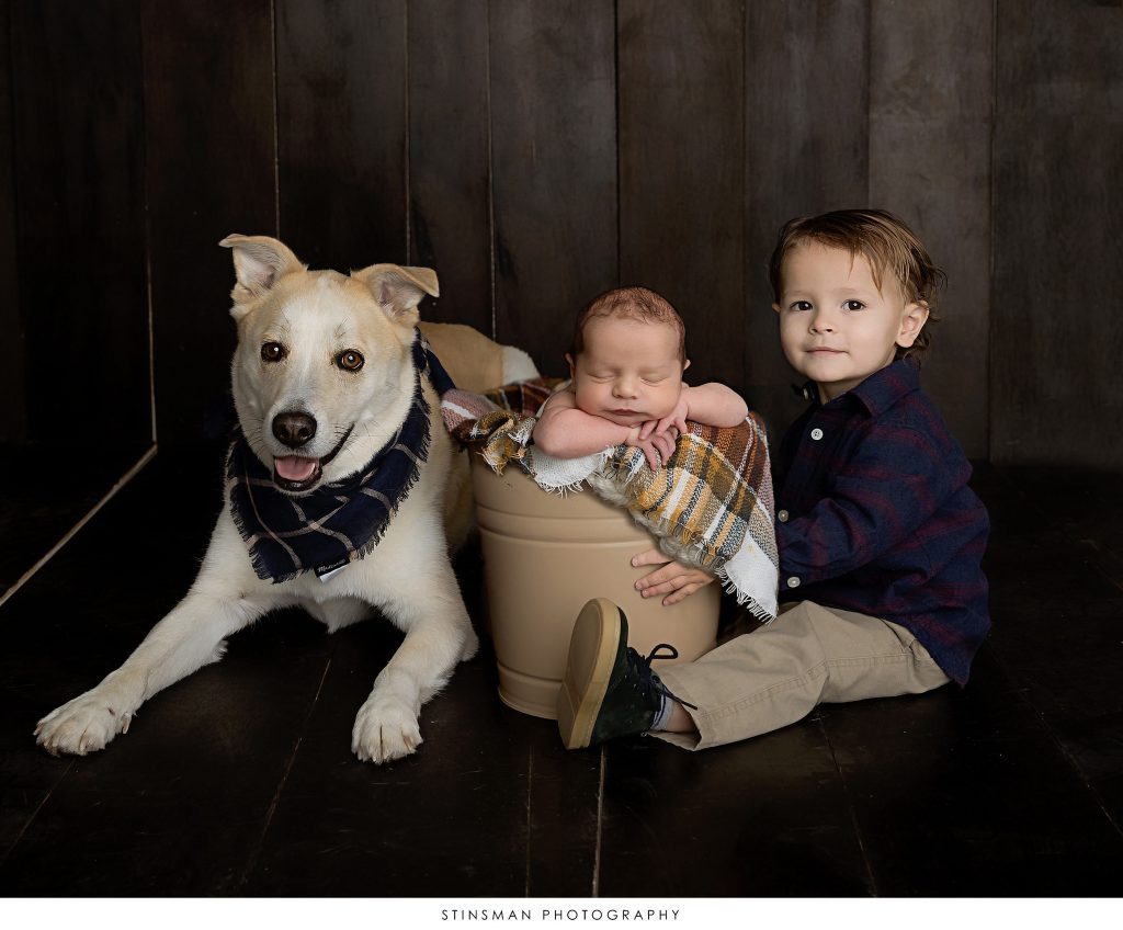 Big brother, baby, and dog at their newborn photshoot.