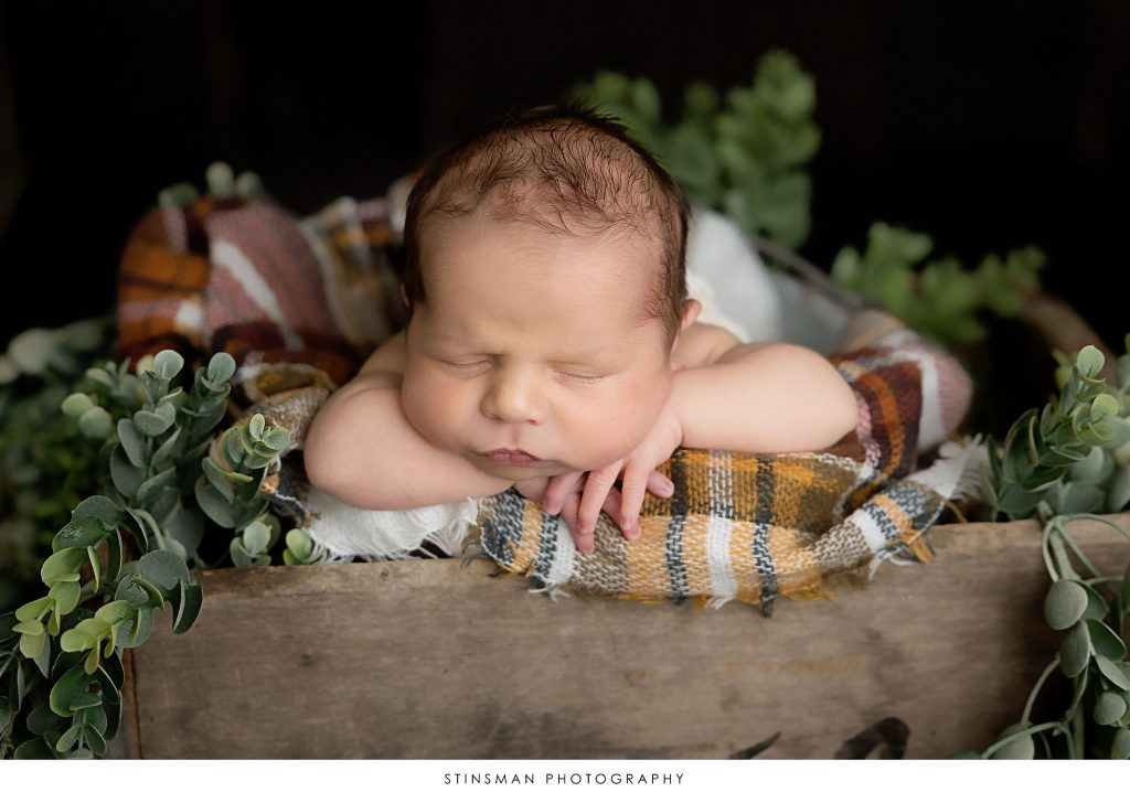 Newborn baby boy posed at his newborn photoshoot.
