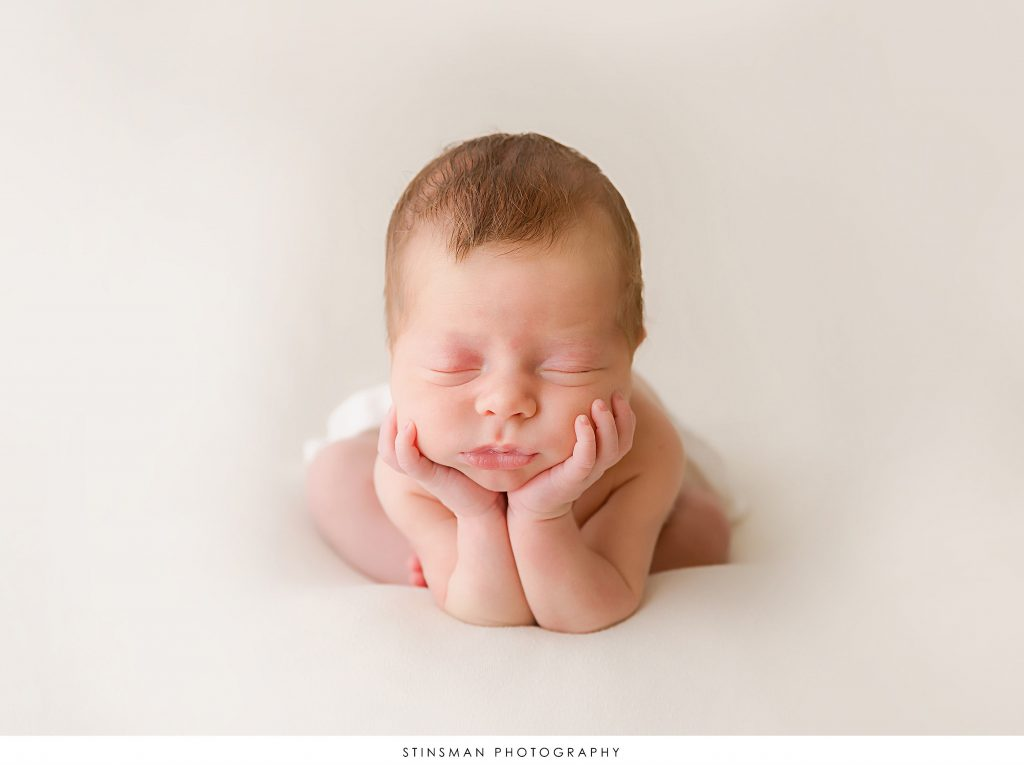 Newborn baby boy in the froggie pose at his newborn photoshoot