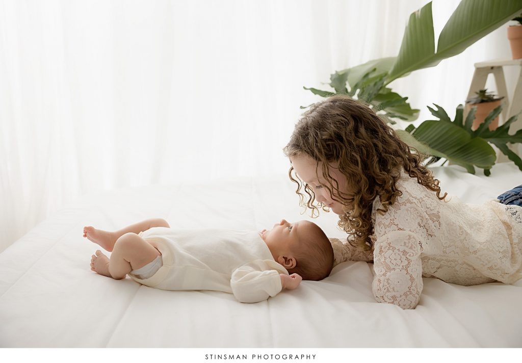 Big sister and new baby brother staring at each other at their newborn photoshoot