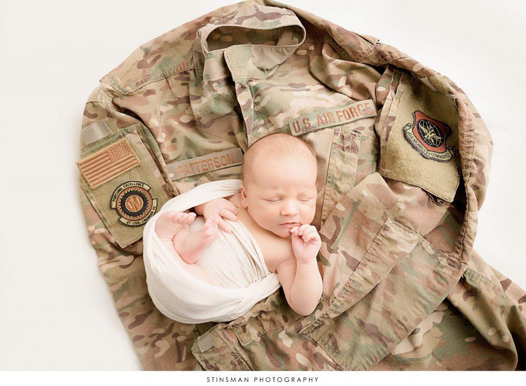 Newborn baby boy on dad's uniform top at newborn photoshoot