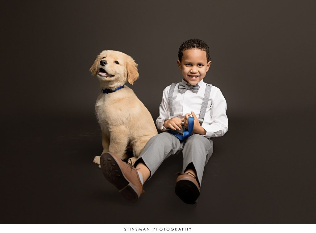 Son and puppy posing at mom's maternity photoshoot
