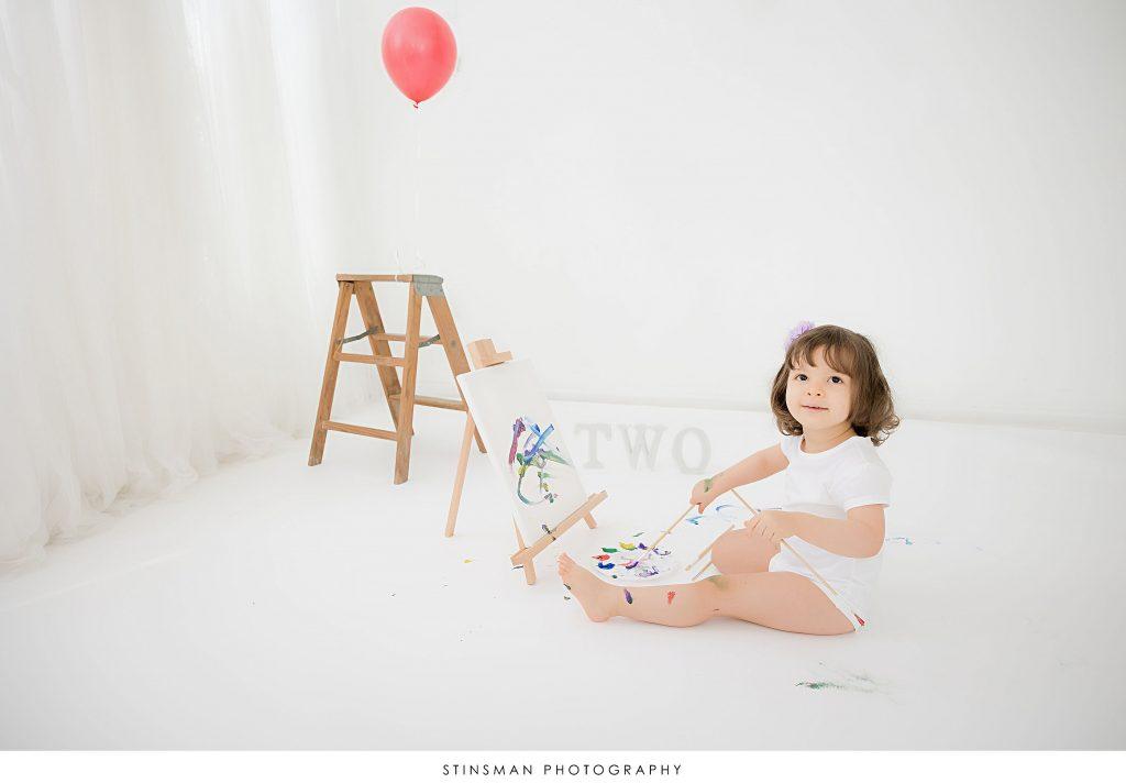 Little girl painting at her 2nd birthday milestone photoshoot