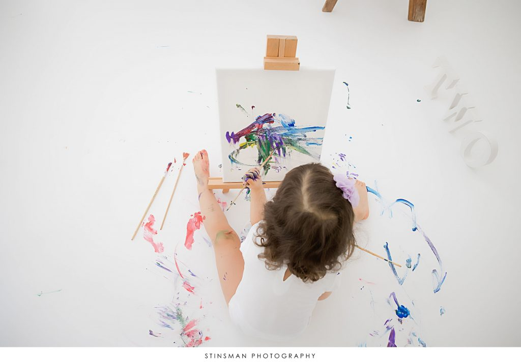 Little girl painting at her second birthday milestone photoshoot
