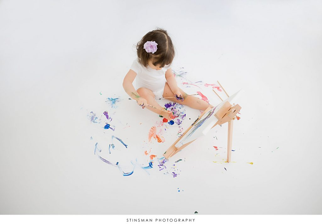 Little girl playing with paint and brushes at her 2nd birthday milestone photoshoot