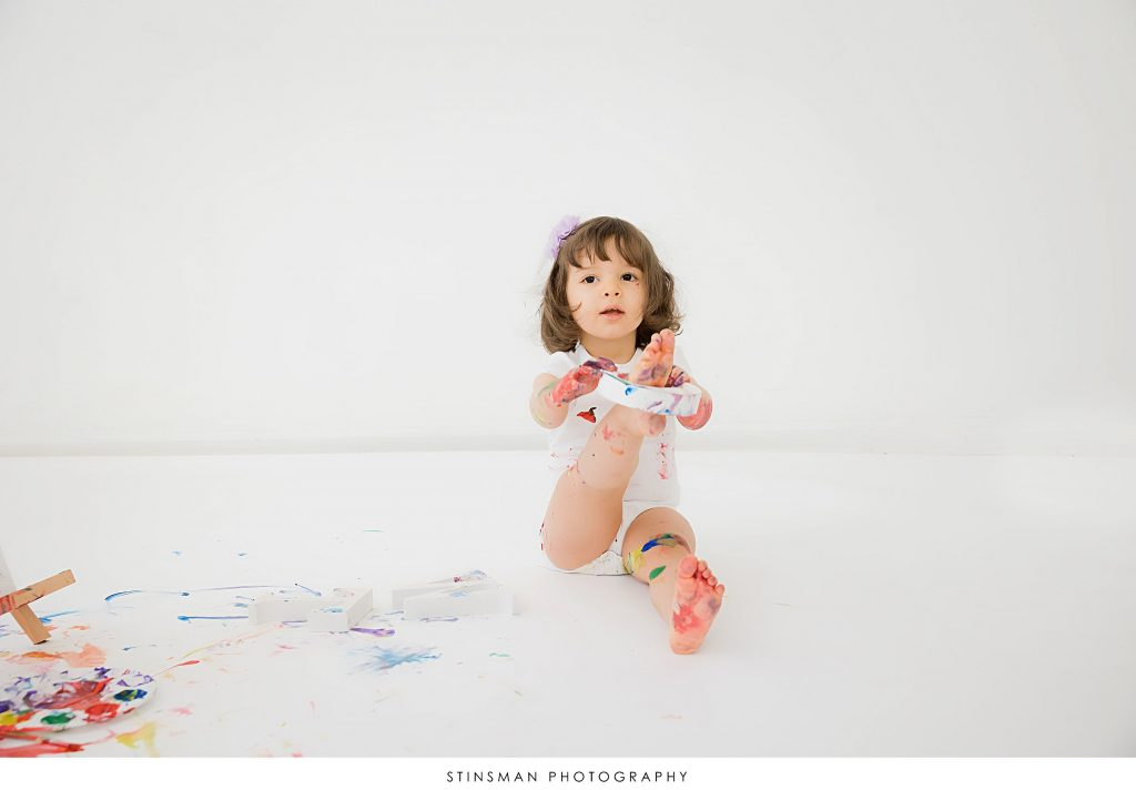 Little girl painting at her 2 year old milestone photoshoot
