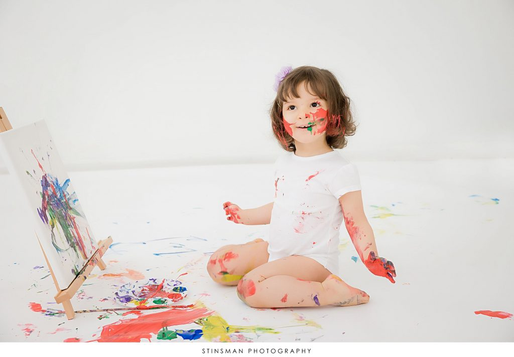 Little girl smiling and painting at her 2 year old milestone photoshoot