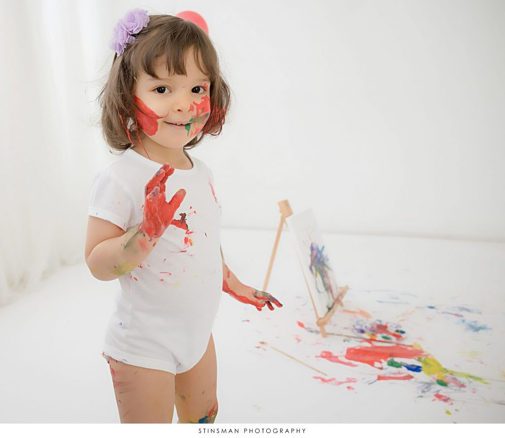 Little girl smiling at her 2 year old paint themed milestone photoshoot