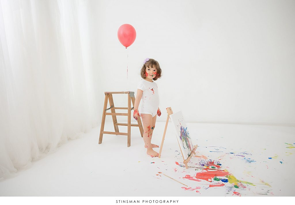 Little girl playing at her paint themed 2 year old milestone birthday photoshoot