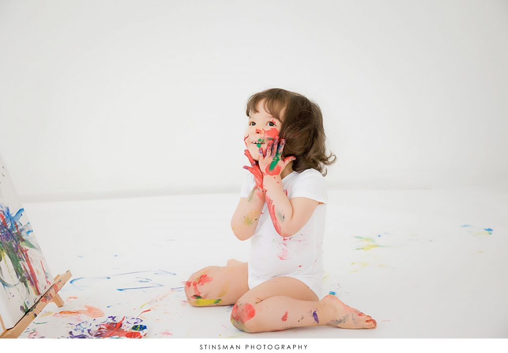 Little girl playing with paint at her 2 year old birthday milestone photoshoot