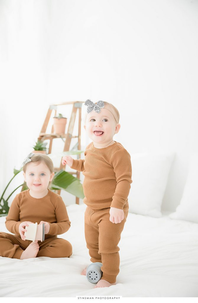 Sisters smiling at first birthday milestone photoshoot