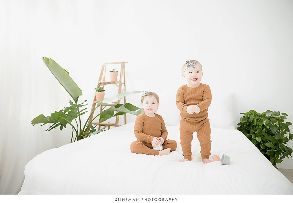 Sisters matching on a bed scene at first birthday milestone photoshoot