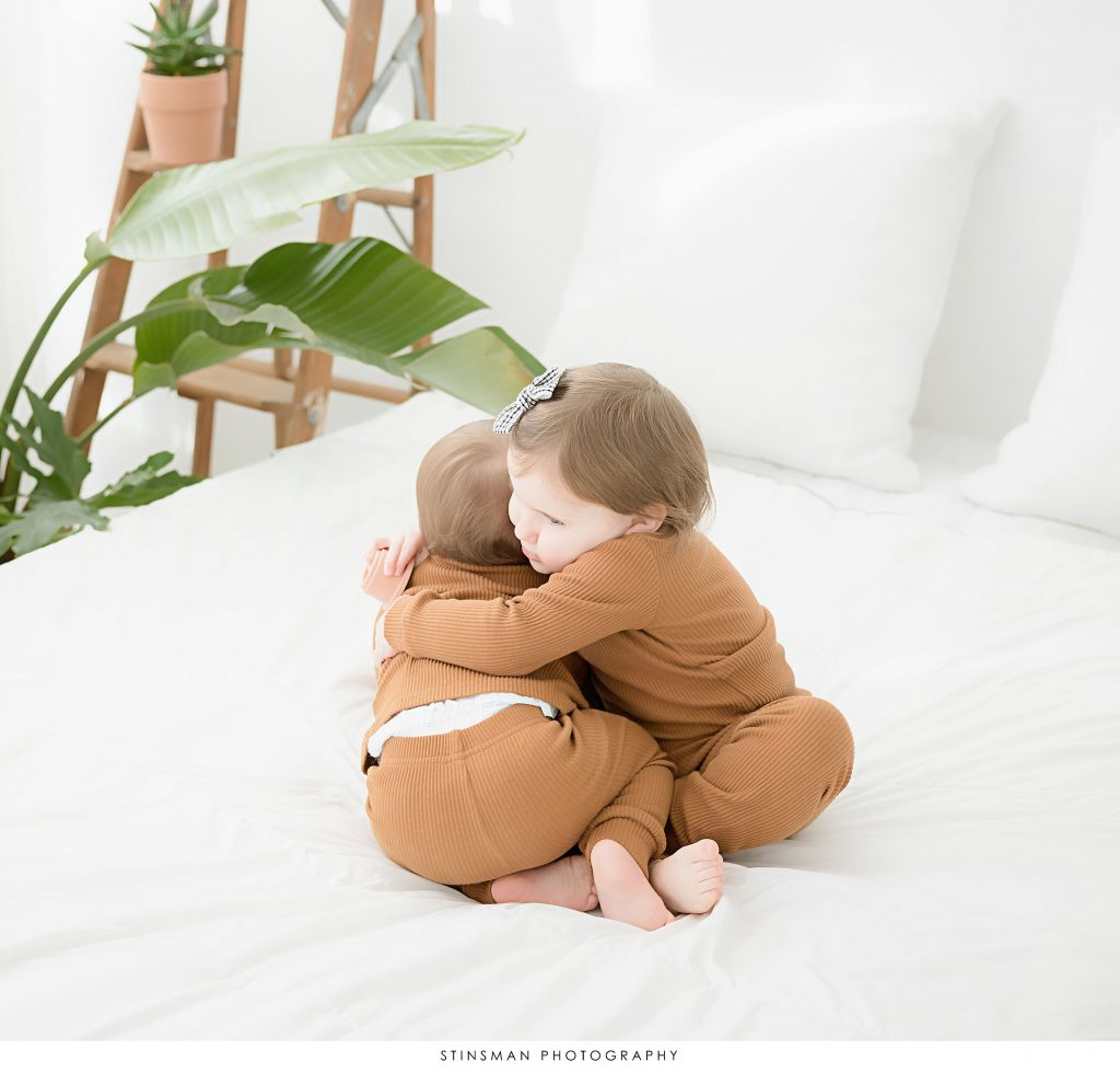 sisters giving hugs at first birthday milestone photoshoot