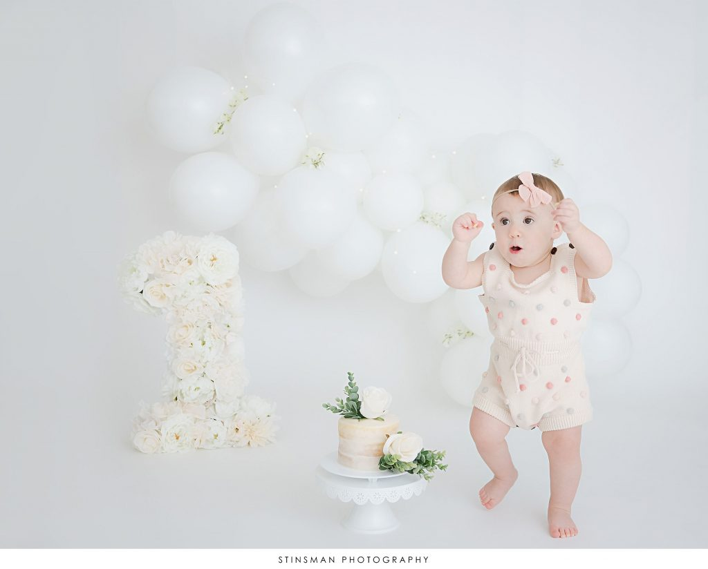 Little girl with her cake at milestone photoshoot