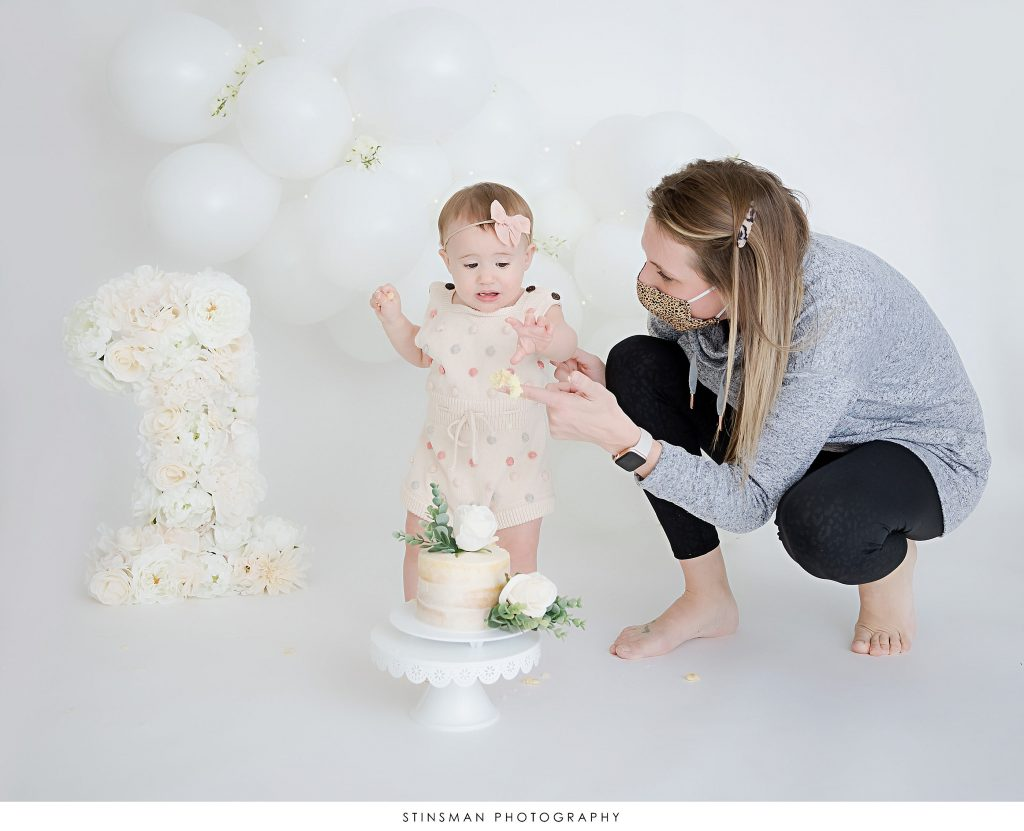 Mom and her one year old daughter at cake smash portion of her first birthday milestone photoshoot