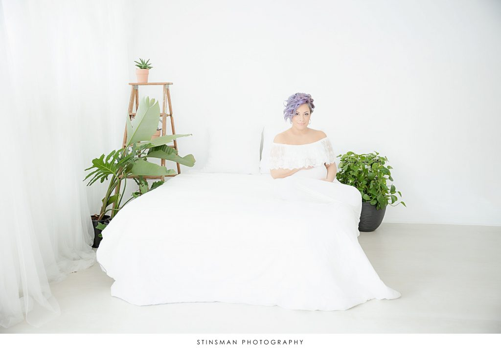 Pregnant mom in white dress posing at her maternity photoshoot