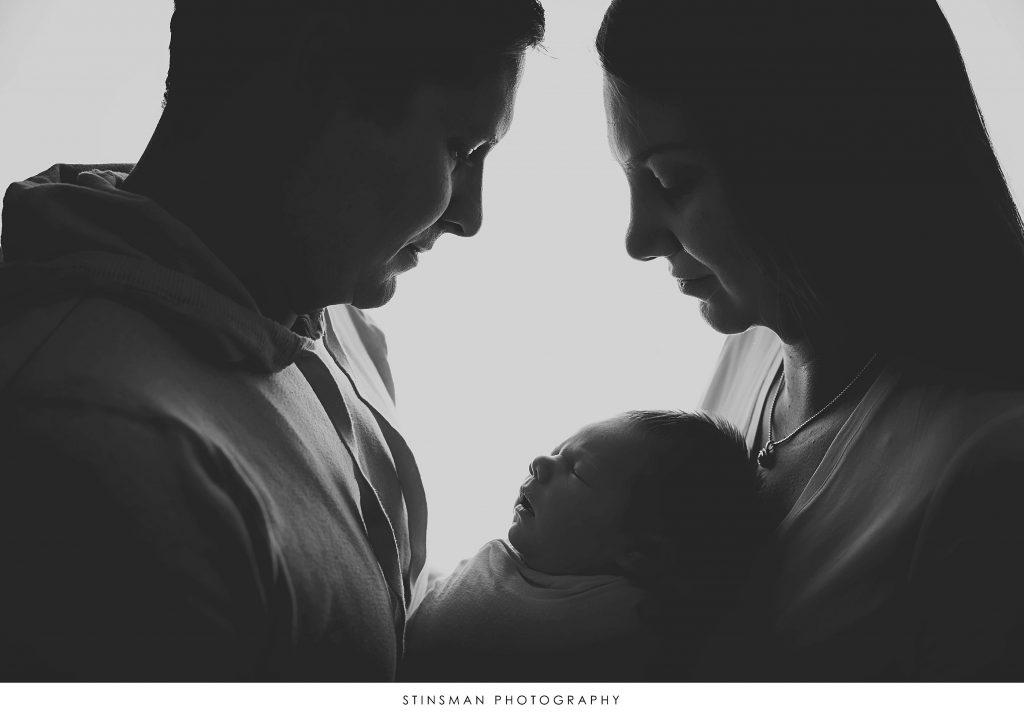 Mom and dad holding their newborn baby boy at their newborn photoshoot