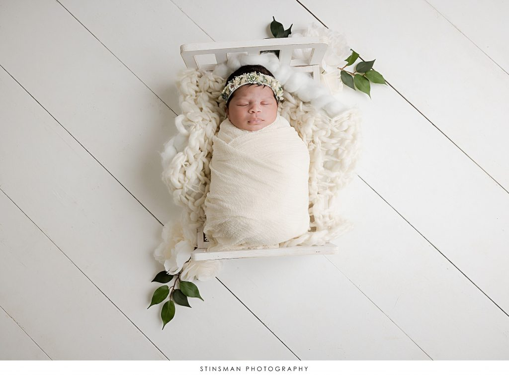 Newborn baby girl sleeping in wooden bed at her newborn photoshoot