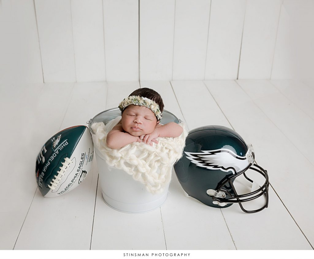 Newborn baby girl asleep in a bucket posing at her newborn photoshoot