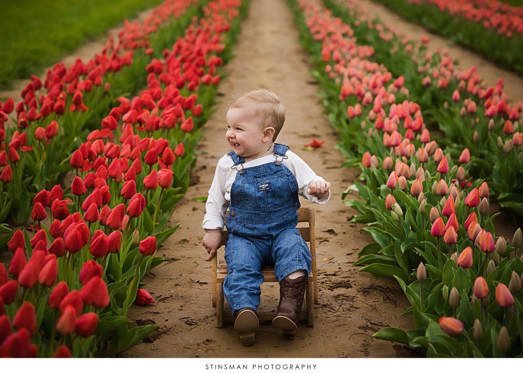 little boy smiling at his tulip mini photoshoot