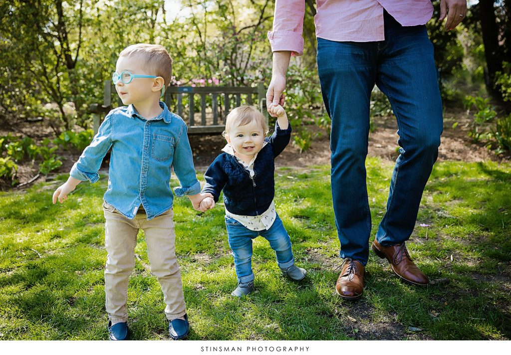 Brothers holding hands with dad at their outdoor family photoshoot