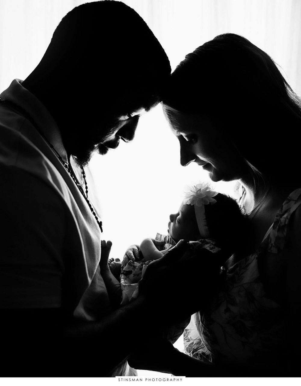 Mom and dad snuggling baby girl at their newborn photoshoot