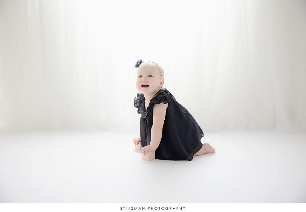 Baby girl smiling at her first birthday milestone photoshoot