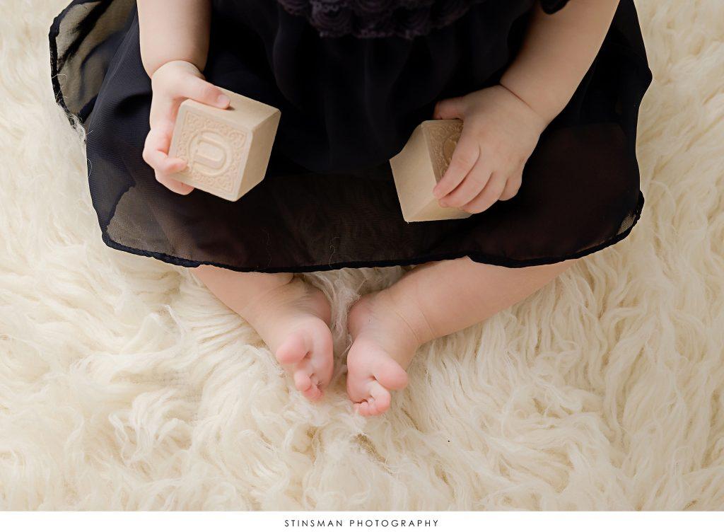 Baby girl holding blocks at her first birthday milestone photoshoot