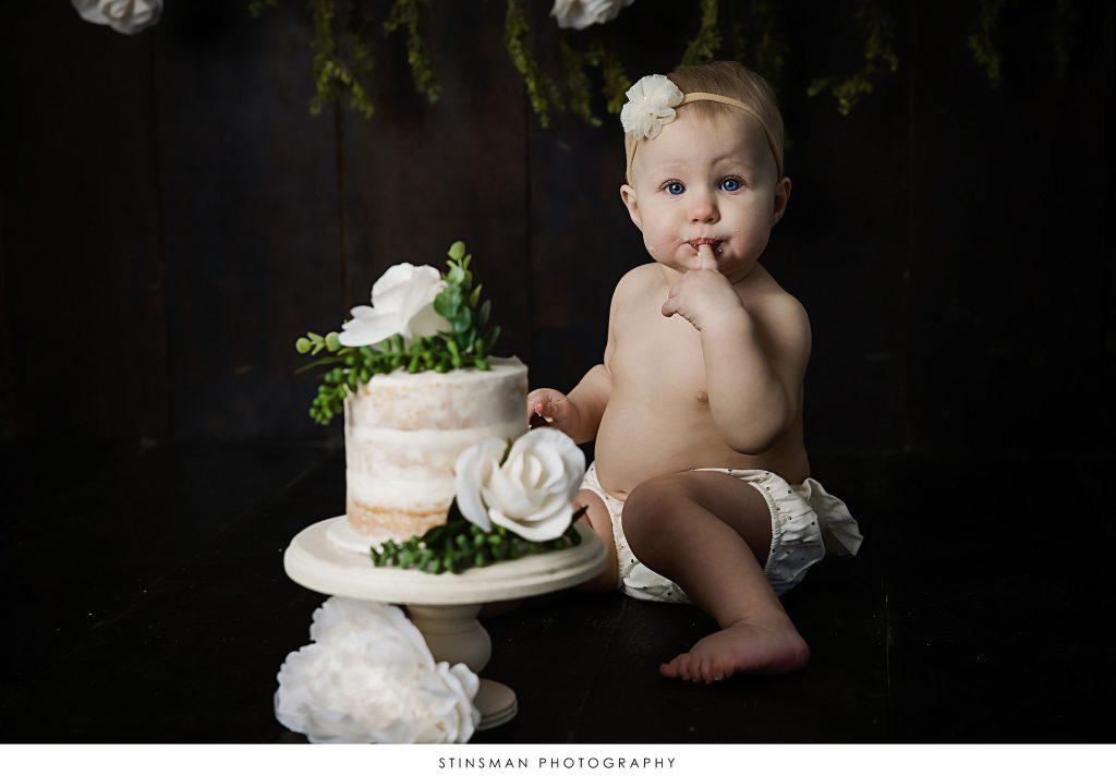 Baby girl tasting her cake at her cake smash photoshoot
