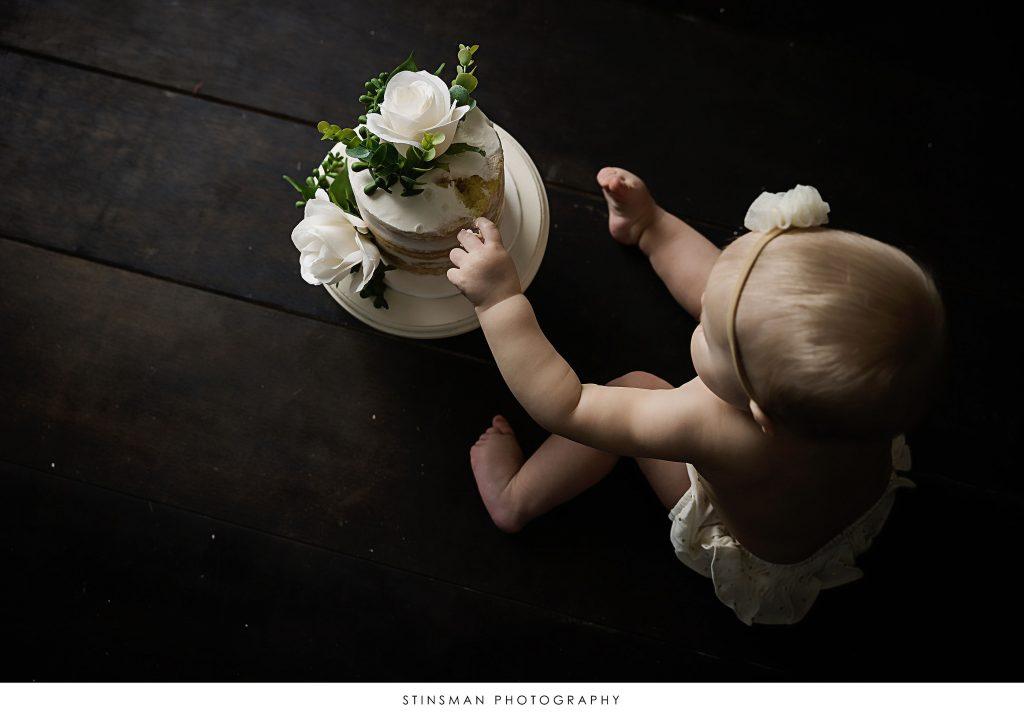 Baby girl touching her cake at her cake smash photoshoot